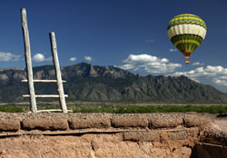 Picture of a balloon rising in front of mountains and behind a ladder