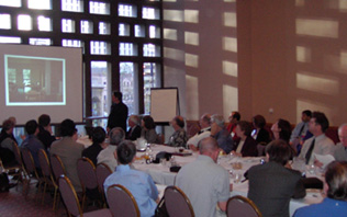 photo: Attendees meeting around a conference table, viewing a presentation